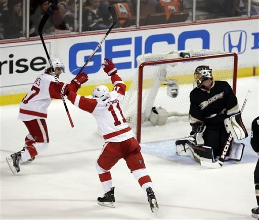 Detroit Red Wings right wing Daniel Cleary, middle, celebrates his goal past Anaheim Ducks goalie Jonas Hiller, right, with Patrick Eaves during the first period in Game 1 of their first-round NHL hockey Stanley Cup playoff series in Anaheim, Calif., Tuesday, April 30, 2013. (AP Photo/Chris Carlson