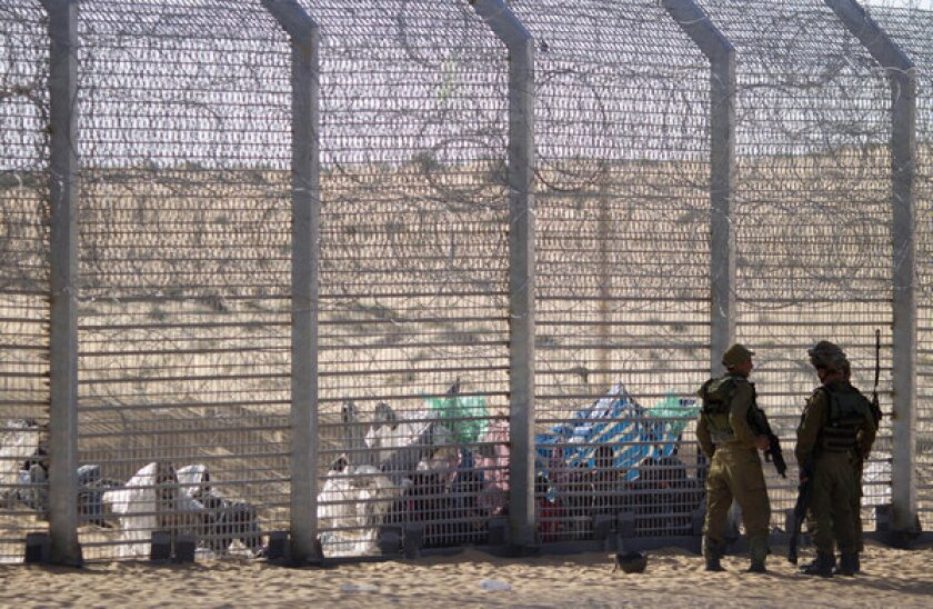African refugees sit on the ground behind a border fence after they attempted to cross illegally from Egypt into Israel, as Israeli soldiers stand guard near the border with Egypt, in southern Israel.