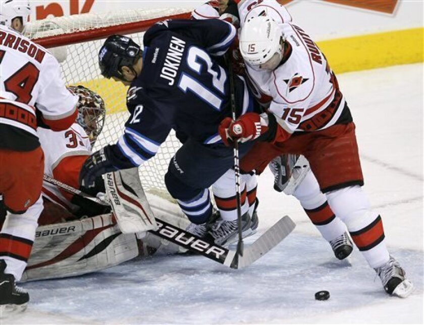 Carolina Hurricanes' Tuomo Ruutu (15) knocks Winnipeg Jets' Olli Jokinen (12) off the rebound in front of goaltender Justin Peters (35) during the first period of their NHL hockey game in Winnipeg, Manitoba, Thursday, April 18, 2013. (AP Photo/The Canadian Press, John Woods)