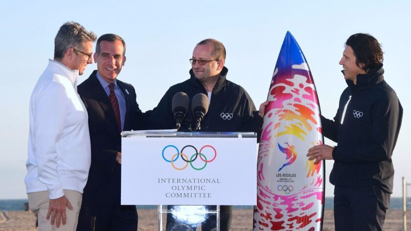 Patrick Baumann, center, and Christophe Dubi, right, of an International Olympic Committee delegation are given a surfboard by LA 2024 Chairman Casey Wasserman, left, and L.A. Mayor Eric Garcetti at Santa Monica Beach.