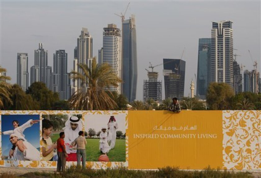 A worker fixes the fence of a new development project, Dar Wasl in Dubai, United Arab Emirates, Monday, Nov. 30, 2009. The heavily indebted Dubai World is not guaranteed by the emirate's government, a top financial official from the city state said Monday, offering little direction to anxious inves