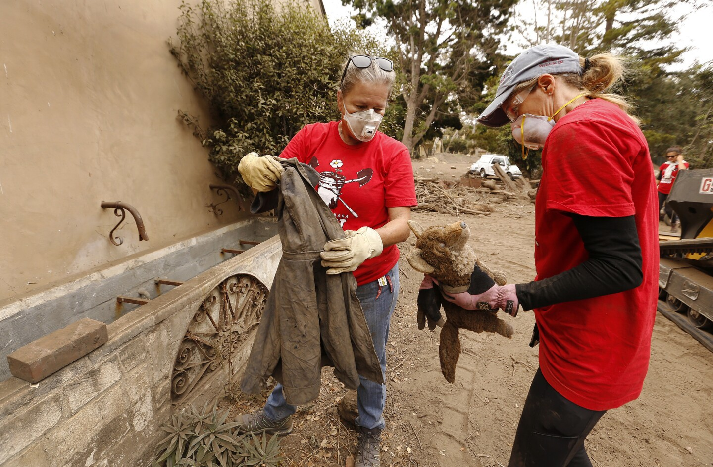 "Andrea Pighetti, left, and Sherri Ball, right, who lost her home in the Jan. 9, 2018, Montecito mudslide, sort through items found in debris piles as volunteers with the Santa Barbara Bucket Brigade search through piles of dirt for manmade objects and the two young victims, Lydia Sutthithepa, 2, and John ""Jack"" Cantin, 17."