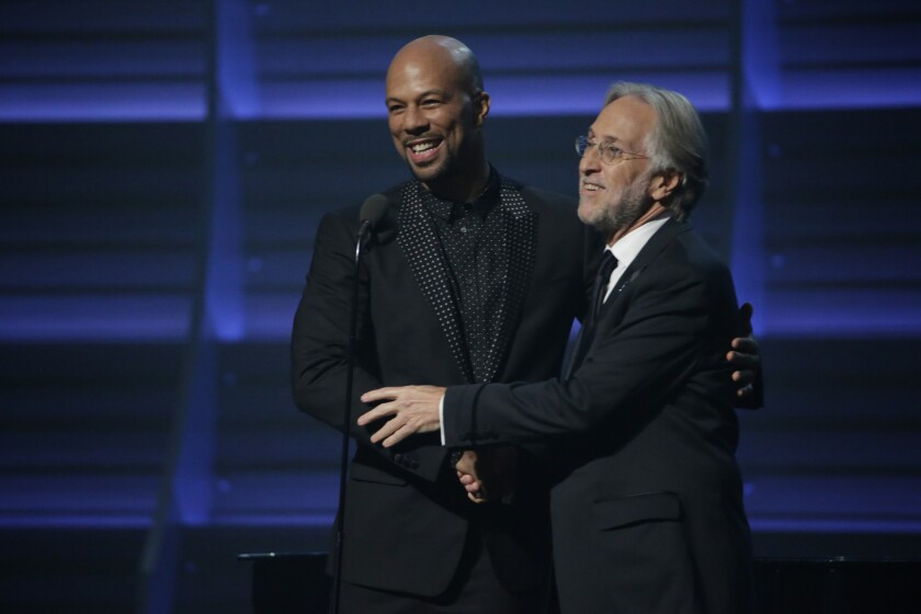 Common, left, and Recording Academy President Neil Portnow embrace at the 58th Grammy Awards at Staples Center on Monday.
