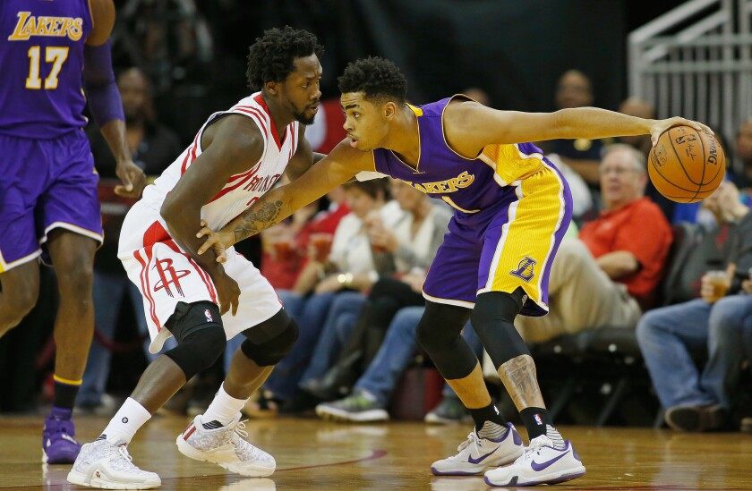 Lakers rookie point guard D'Angelo Russell keeps the ball away from Rockets guard Patrick Beverley on the wing.