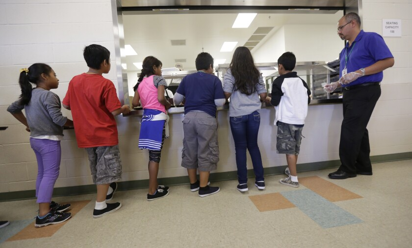 In this Sept. 10, 2014, photo, detained immigrant children line up in the cafeteria at the Karnes County Residential Center