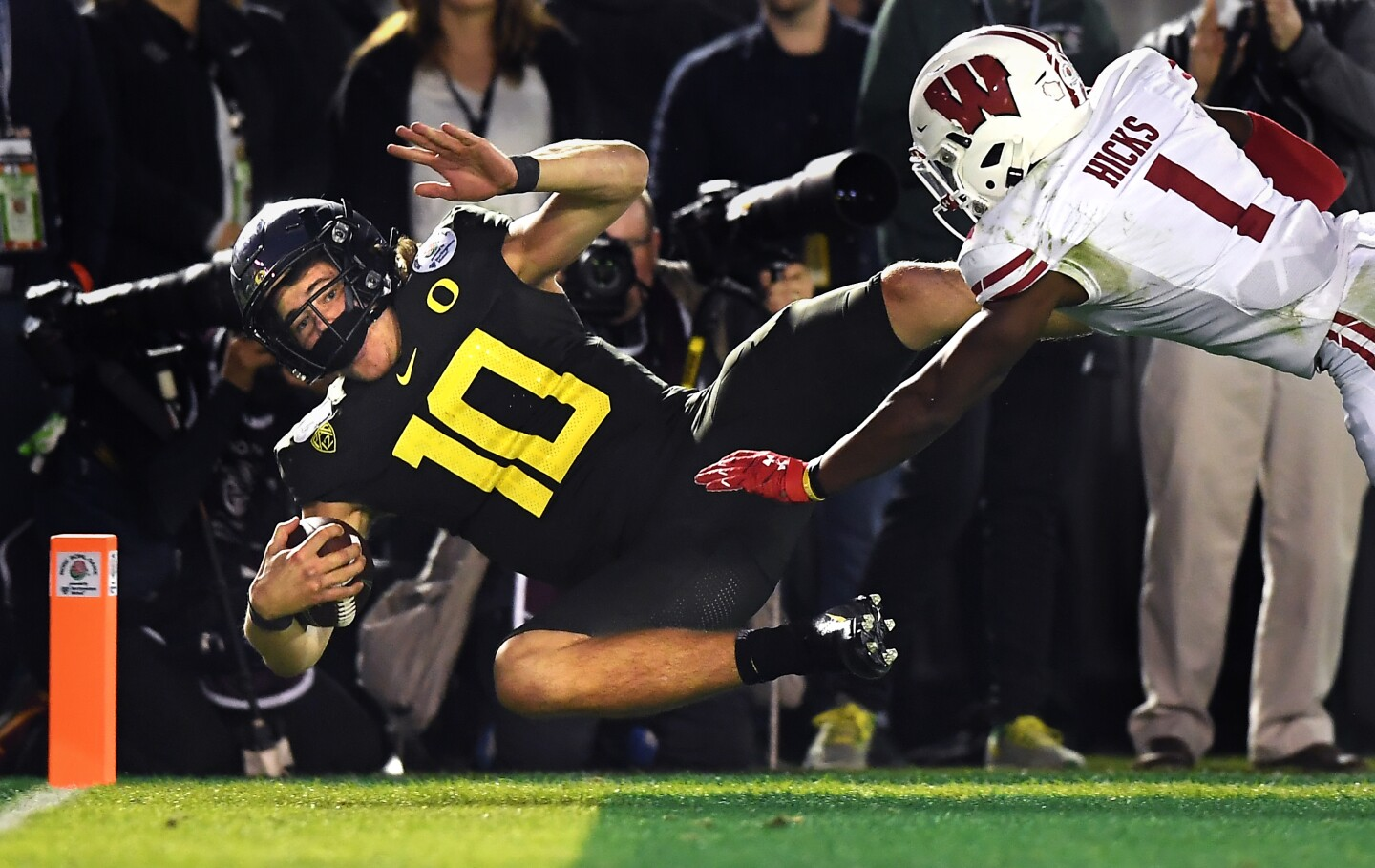 PASADENA, CALIFORNIA JANUARY 1, 2020-Oregon quarterback Justin Herbert scores the go-ahead touchdown against Wisconsin cornerback Faion Hicks in the 4th quarter at the Rose Bowl in Pasadena Wednesday. (Wally Skalij/Los Angerles Times)