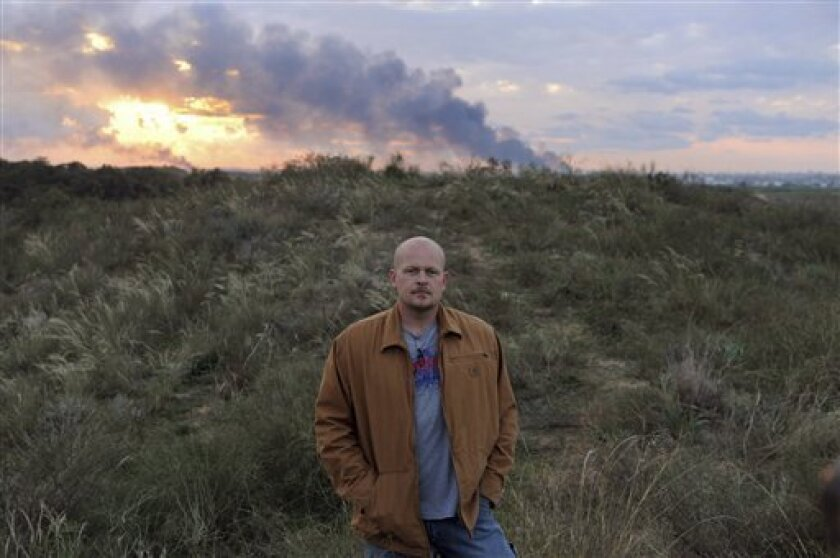 Samuel Wurzelbacher, known as Joe the Plumber, who is in the region to report for US the conservative pjtv.com Web site  and back dropped by smoke billowing from fires caused by Israeli military attacks from inside the Gaza Strip, poses for pictures, near the southern Israeli  city of Sderot, Sunda