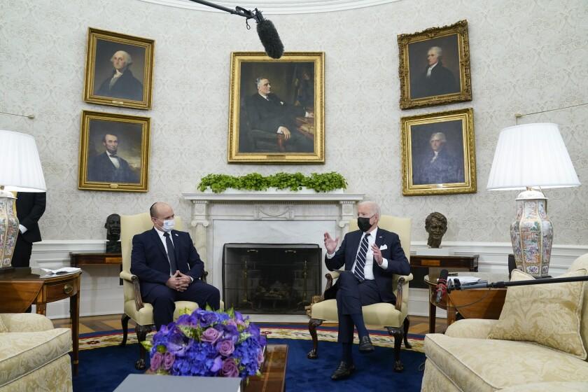 President Biden and Israeli Prime Minister Naftali Bennett, wearing masks, sit in the Oval Office.