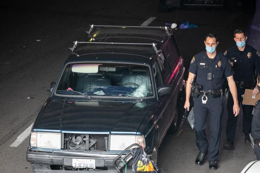 Police walk by damaged Volvo station wagon in B Street tunnel