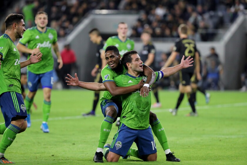 Seattle Sounders' Nicolás Lodeiro gets a hug from Joevin Jones after Lodeiro scores against LAFC on Oct. 29, 2019.