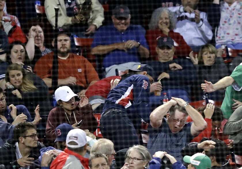 Fans react after getting hit by a bat, which flew over the protective screening, after Toronto Blue