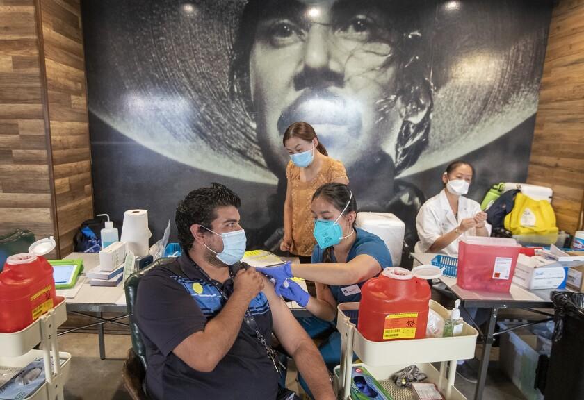 Gabi Caohui gives Johnnie Cruz a COVID-19 vaccination  at El Indio Botanas y Cerveza in Santa Ana.