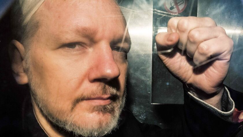 WikiLeaks founder Julian Assange gestures May 1 from the window of a prison van as he is driven out of Southwark Crown Court in London.