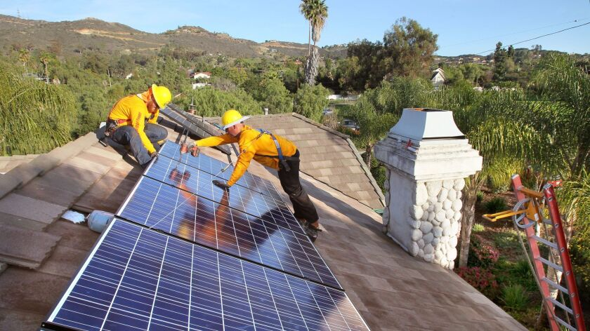Workers from Sullivan Solar Power, of San Diego, install solar panels on the roof of a home in Vista.