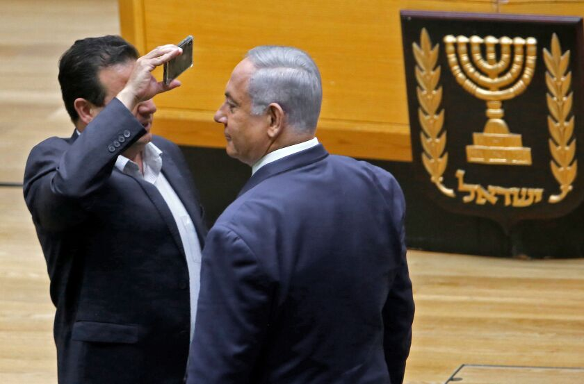 Ayman Odeh, left, leader of the Joint List of Arab parties in Israel's parliament, uses a phone to take a close-up picture of Prime Minister Benjamin Netanyahu in the Knesset chamber in Jerusalem on Sept. 11, 2019. Netanyahu and Odeh clashed during a discussion before a vote on a controversial bill to allow cameras in polling booths.