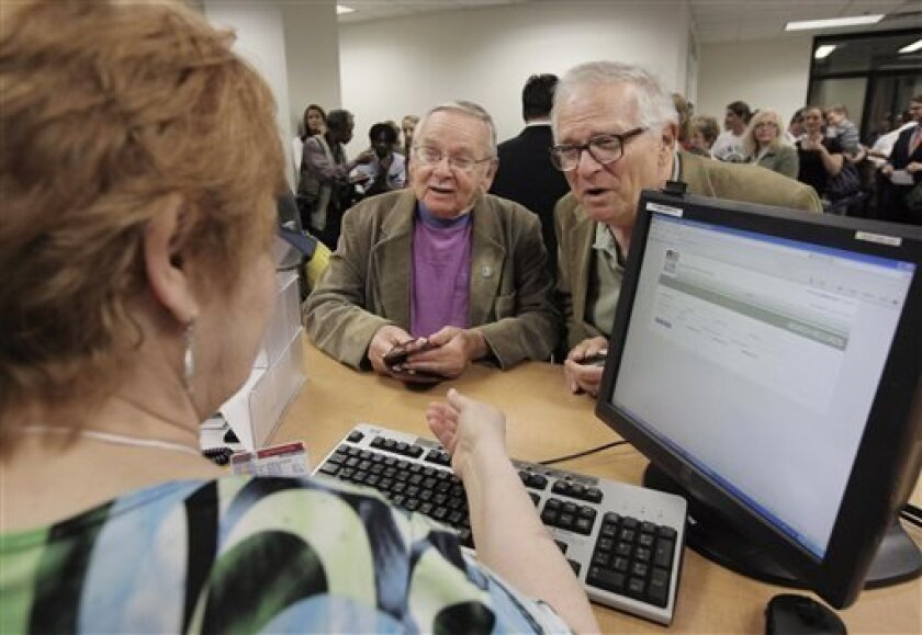 FILE - In this June 1, 2011, file photo, Jim Darby, 79, left, and his partner Patrick Bora, 73, apply for a civil union license at the Cook County Office of Vital Records in Chicago. Attorneys representing them and 24 other same-sex couples in a lawsuit challenging the state gay marriage ban asked a judge Wednesday, July 10, 2013, to rule quickly in their favor. (AP Photo/M. Spencer Green, File)