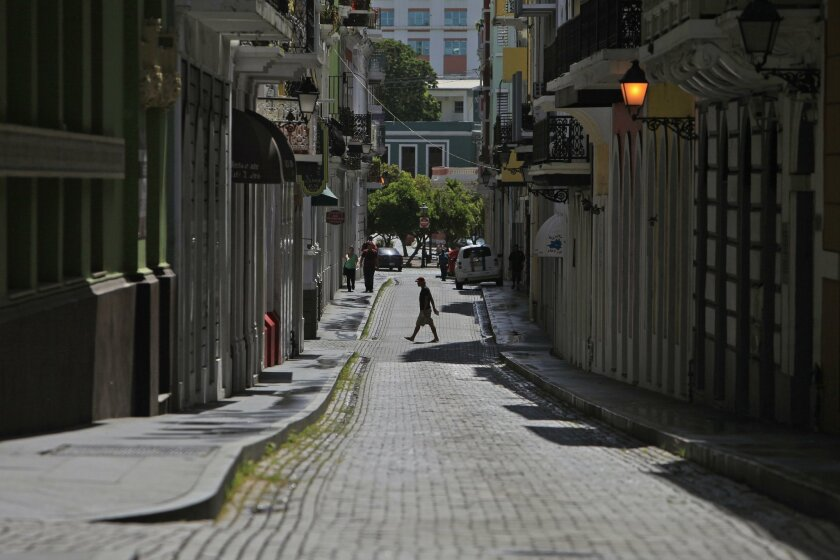 A man crosses a cobblestone street in the colonial district of Old San Juan, Puerto Rico, Sunday, Aug. 2, 2015. During the ongoing economic crisis, tens of thousands have migrated to the U.S. mainland. Crowds have thinned at restaurants and movie theaters; families have cut back on summer excursion