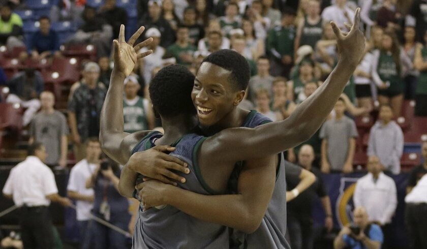 Chino Hills' Elizjah Scott, left, and Onyeka Okongwu celebrate after beating De La Salle 70-50 in the CIF boys' Open Division high school basketball championship game Saturday in Sacramento.