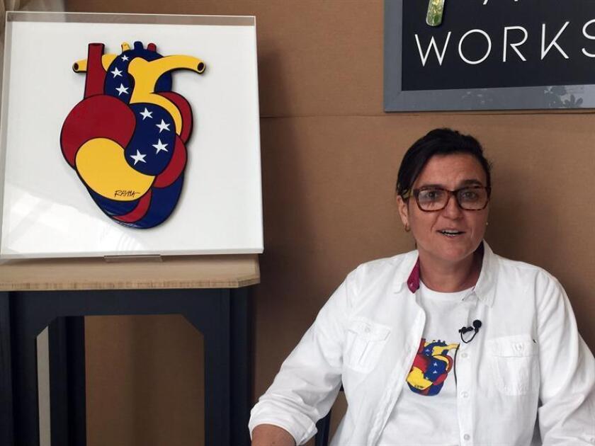 """La caricaturista venezolana Rayma Suprani posa junto a su obra """"corazón venezolano"""" durante una entrevista con Efe este martes, en Miami, Florida (EE.UU.). EFE"""