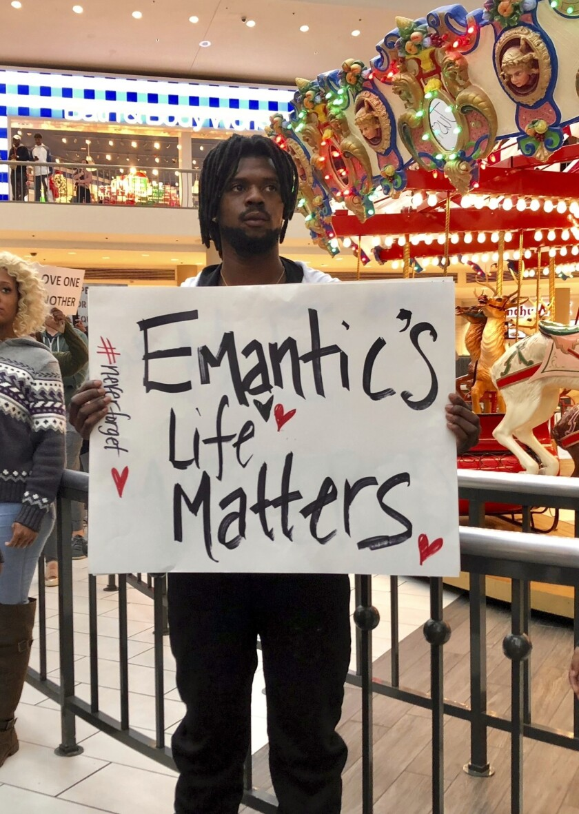 Elijah King holds a sign during a protest at the Riverchase Galleria mall in Hoover, Ala., Saturday, Nov. 24, 2018, over the police shooting of 21-year-old Emantic Fitzgerald Bradford, Jr. of Hueytown.