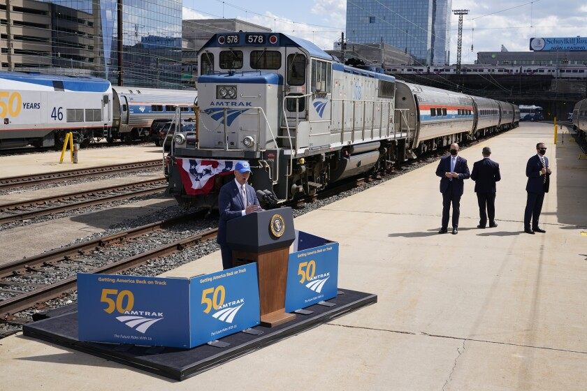 President Biden stands at a small podium set up trackside in front of locomotive and train