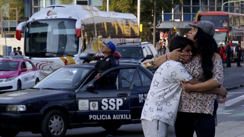 A woman embraces a boy as a powerful earthquake rocked Mexico City on Friday.