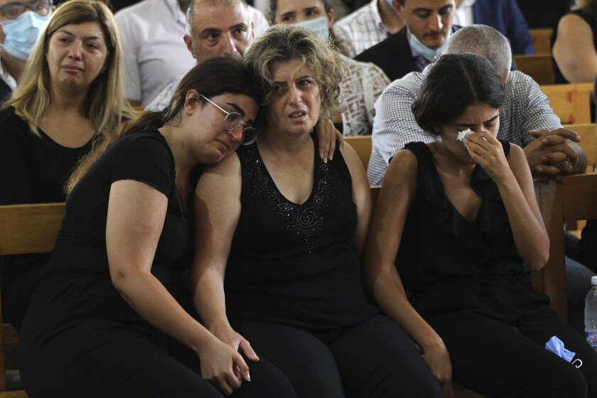 Nicole Helou's sisters flank their mother at Helou's funeral in Sarba, Lebanon. Helou was killed in the blast in Beirut.