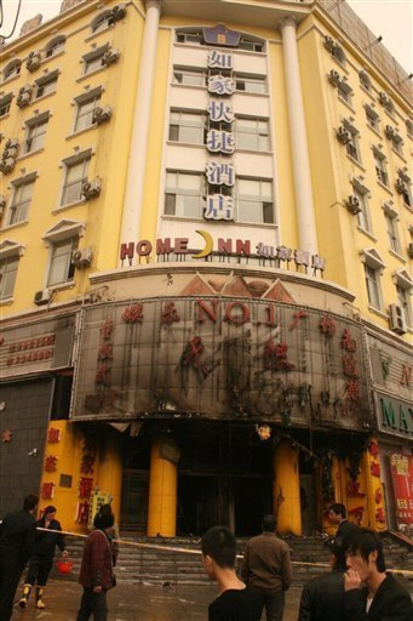 In this photo distributed by China's Xinhua news agency, spectators look at a hotel after fire in Tonghua, northeast China's Jilin province, on Sunday May 1, 2011. The fire at the hotel in northeastern China killed at least 10 people and injured 35 others Sunday, while lightning sparked several forest fires in another part of the country, a state news agency said. (AP Photo/Xinhua) NO SALES