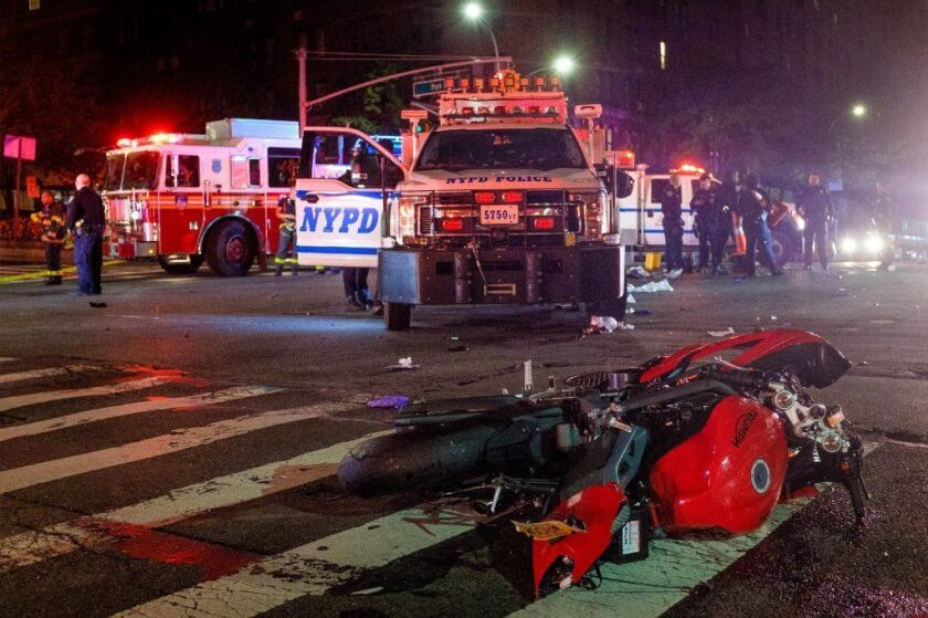 A red Triumph motorcycle is seen after it collided with an NYPD Emergency Service Unit vehicle (pictured) at E. 96th St. and Park Ave. on Monday night.