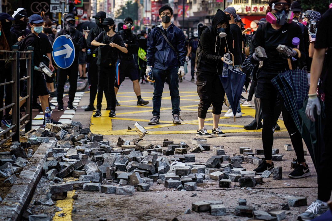 Protesters pull out bricks from the sidewalk to use as road blocks and for throwing, near the Jordan district of Hong Kong.