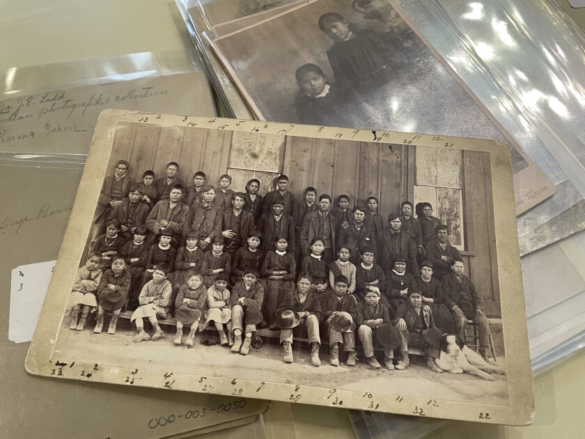 This July 8, 2021 image of a photograph archived at the Center for Southwest Research at the University of New Mexico in Albuquerque, New Mexico, shows a group of Indigenous students who attended the Ramona Industrial School in Santa Fe. The late 19th century image is among many in the Horatio Oliver Ladd Photograph Collection that are related to the boarding school. (AP Photo/Susan Montoya Bryan)