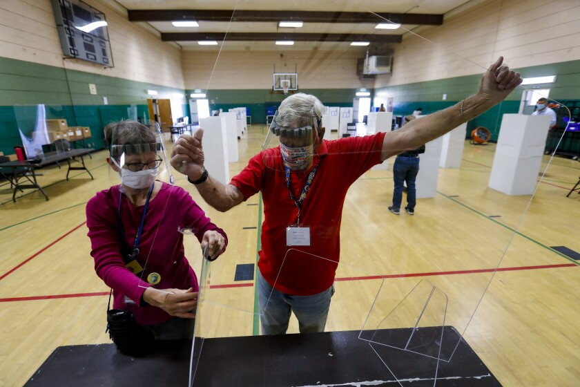 Suzanne Mandel-Mosko and John Gahan setup the plexiglass that will serve as a safety shield