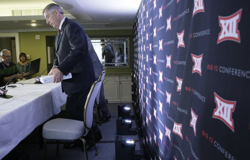 Commissioner of the Big 12 Bob Bowlsby takes a seat before speaking to reporters after the first day of the Big 12 sports conference meeting in Irving, Texas, Wednesday, June 1, 2016. (AP Photo/LM Otero)