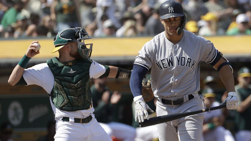 New York Yankees' Giancarlo Stanton, right, walks to the dugout after striking out as Oakland Athletics catcher Jonathan Lucroy throws the ball during the sixth inning of a baseball game in Oakland, Calif., Monday, Sept. 3, 2018. (AP Photo/Jeff Chiu)