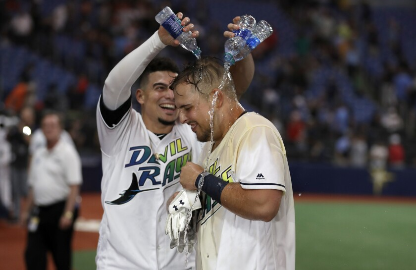 Tampa Bay Rays' Nate Lowe, right, gets doused with water by Willy Adames after Lowe hit a two-run, walk-off home run off Boston Red Sox relief pitcher Josh Smith in the 11th inning of a baseball game, Saturday, Sept. 21, 2019, in St. Petersburg, Fla. Tampa Bay won 5-4. (AP Photo/Chris O'Meara)