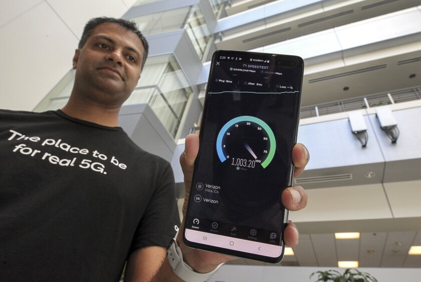 Qualcomm engineer Vid Adiraju holds a smartphone as it goes through a 5G speed test.