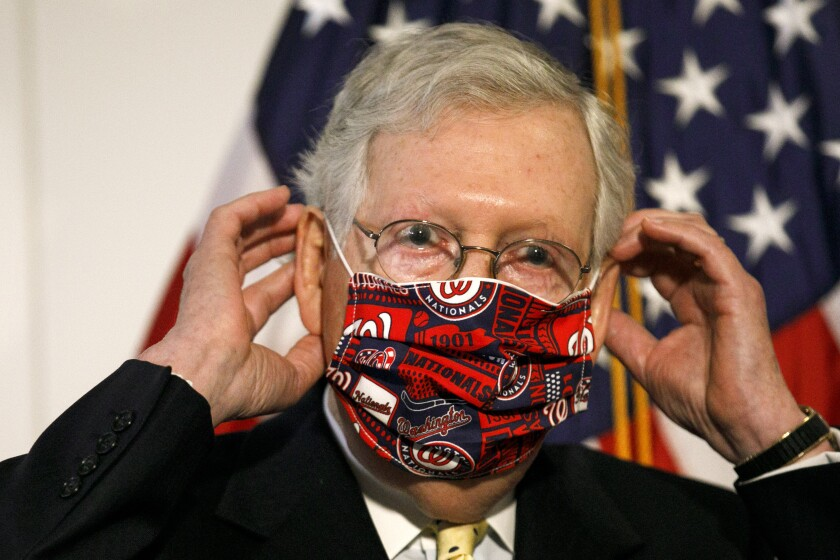 Senate Majority Leader Mitch McConnell replaces his face mask after speaking at a Capitol Hill news conference in the summer