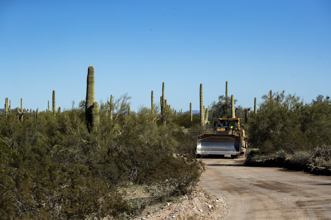 A bulldozer heads along Puerto Blanco Drive toward Monument Hill, where construction crews are making way for new border wall in Organ Pipe Cactus National Monument in Arizona.