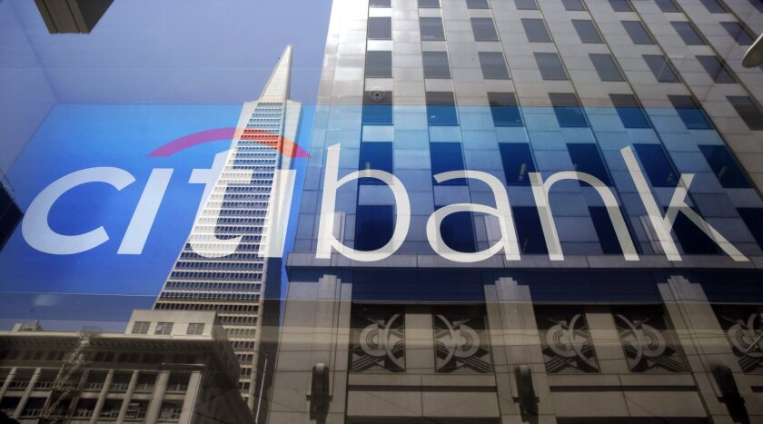 The Transamerica Pyramid is reflected in the window of a Citibank branch in San Francisco.