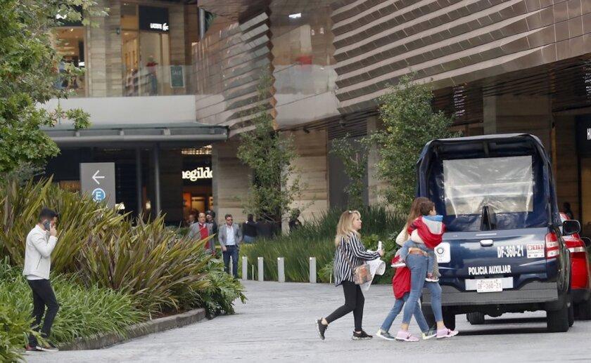 Personas salen de un lujoso centro comercial en el sur de Ciudad de México, en donde una mujer disfrazada con una peluca rubia asesinó a dos israelíes.
