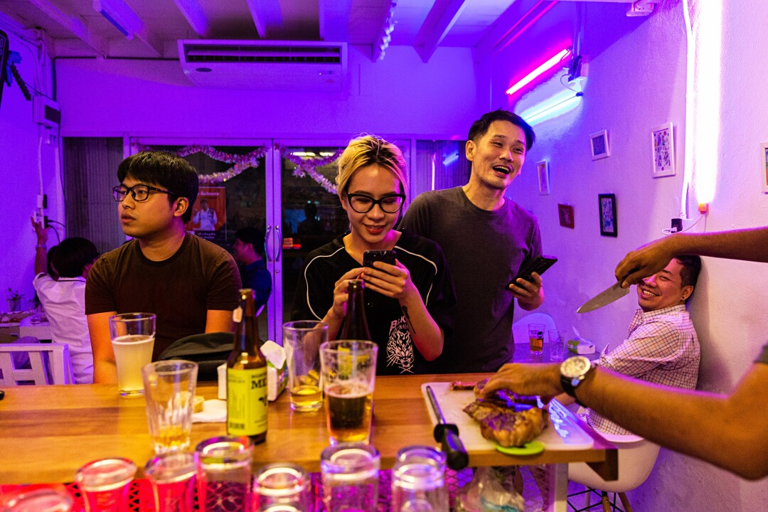 Friends gather at Taopiphop Bar Project in Bangkok, Thailand.