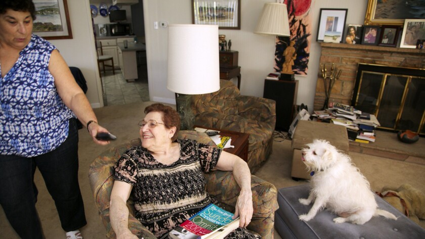"""Eleanor Blum, 88, sits with with her dog """"Cutie"""" as her daughter, Jeri Vargas, brings her a wireless phone in Sherman Oaks."""