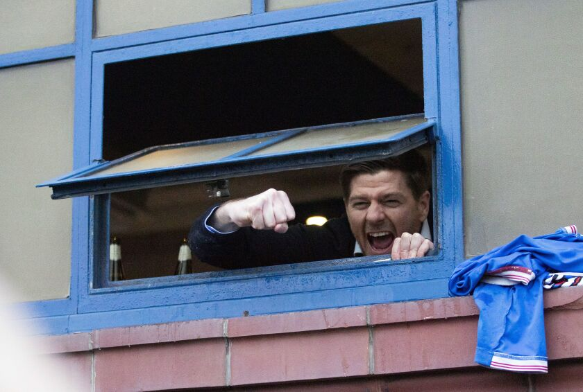 Rangers manager Steven Gerrard hangs out the window of the dressing room to cheer with fans gathered outside the stadium after their win in the Scottish Premiership match against St Mirren, at Ibrox Stadium in Glasgow, Scotland, Saturday March 6, 2021. Some thousands of fans gathered outside the stadium celebrating the win against St. Mirren, putting them on the brink of securing the Scottish Premiership title. (Jane Barlow/PA via AP)