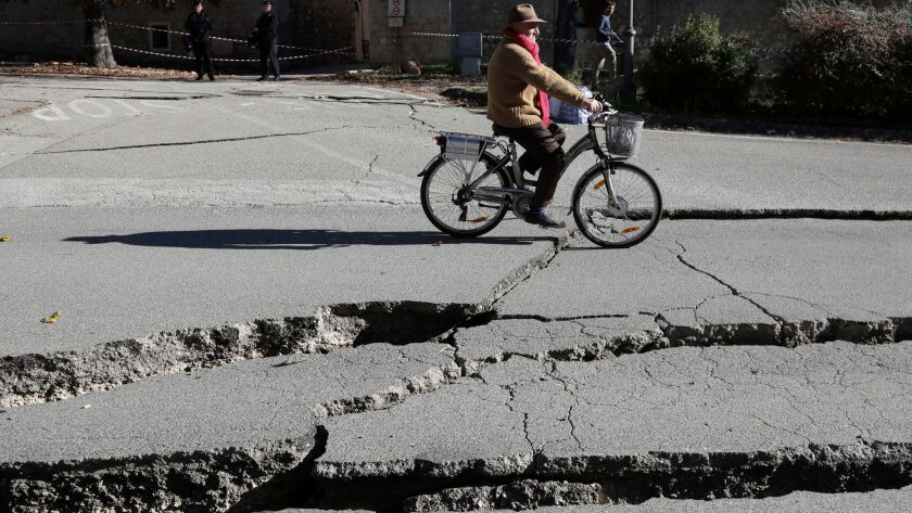 A man rides  past cracks in a road in Norcia, central Italy, after an earthquake with a magnitude of 6.6 hit on Sunday.
