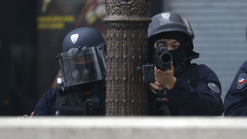 Riot police officers take position during a yellow vests demonstration on the Champs Elysees avenue