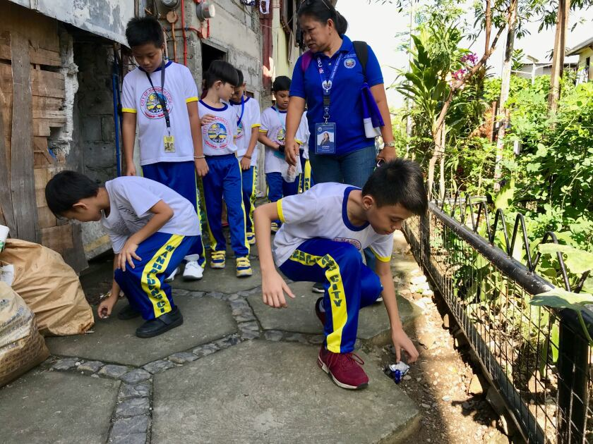 Elementary school students collect litter from along Maytunas Creek, a tributary of the heavily polluted Pasig River in Manila.