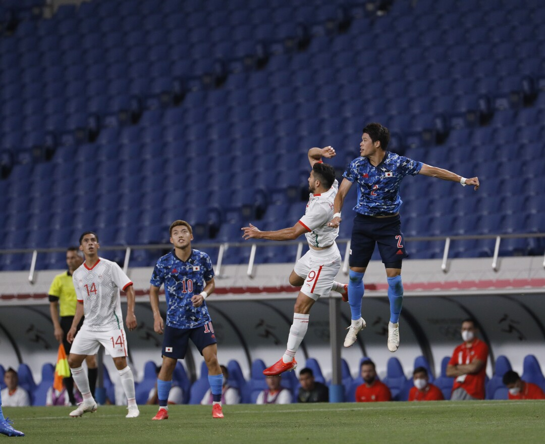 Two men leap into the air. In the background is empty stadium seating.