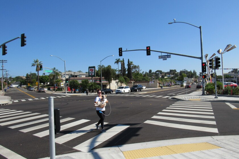A woman carrying her dog crosses at a signalized intersection last year at Parks Avenue and University Avenue in La Mesa. The city has enabled automatic pedestrian recall programming between 6 a.m. and 7:30 p.m. at that intersection as well as five others in hopes of lessening the spread of COVID-19.