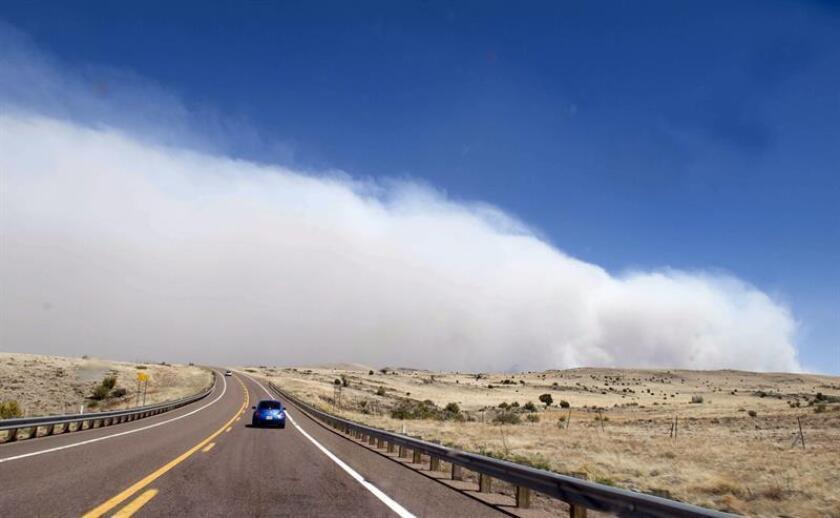 Una nube de humo se ve al fondo en una carretera el 10 de junio de 2011, cerca a Springerville, en Arizona (EEUU). EFE/Archivo