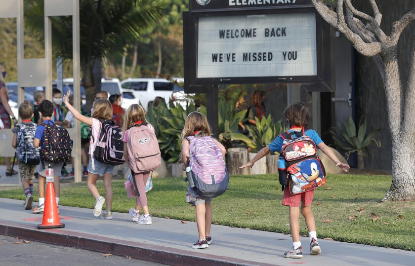"""Kindergartners walk past """"welcome back"""" marquee at Top of the World elementary in October."""